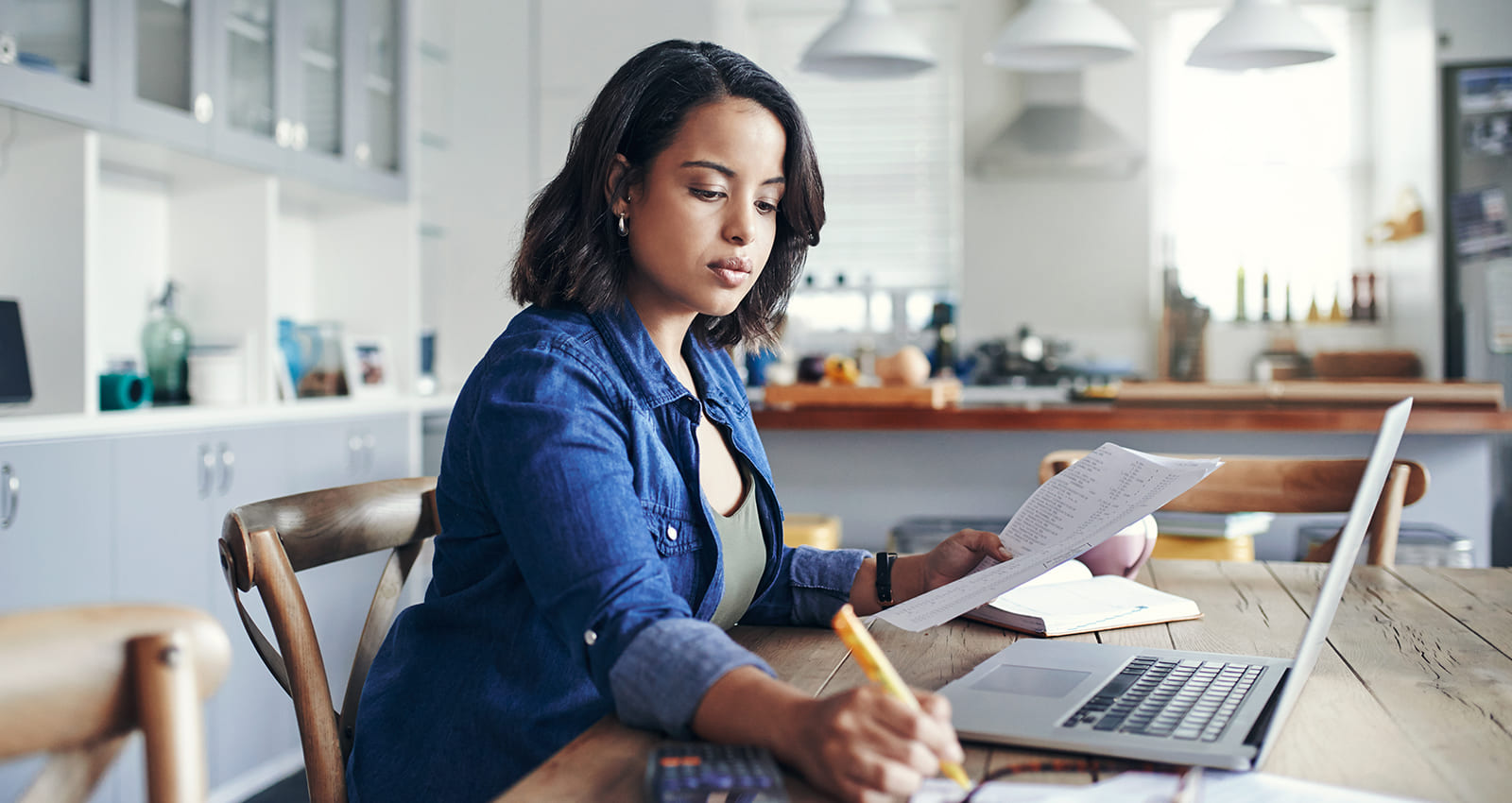 woman working in home on laptop holding papers